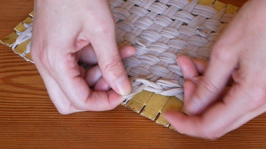 Retirer les boucles de fil des encoches et les croiser entre elles pour fermer le tawashi