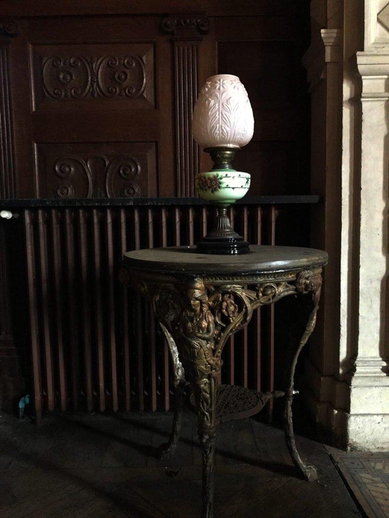 desserte et lampe du grand salon dans un château abandonné, urbex