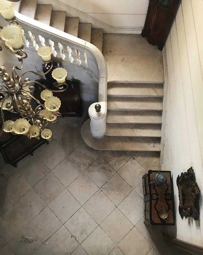 grand escalier central dans un château abandonné, urbex