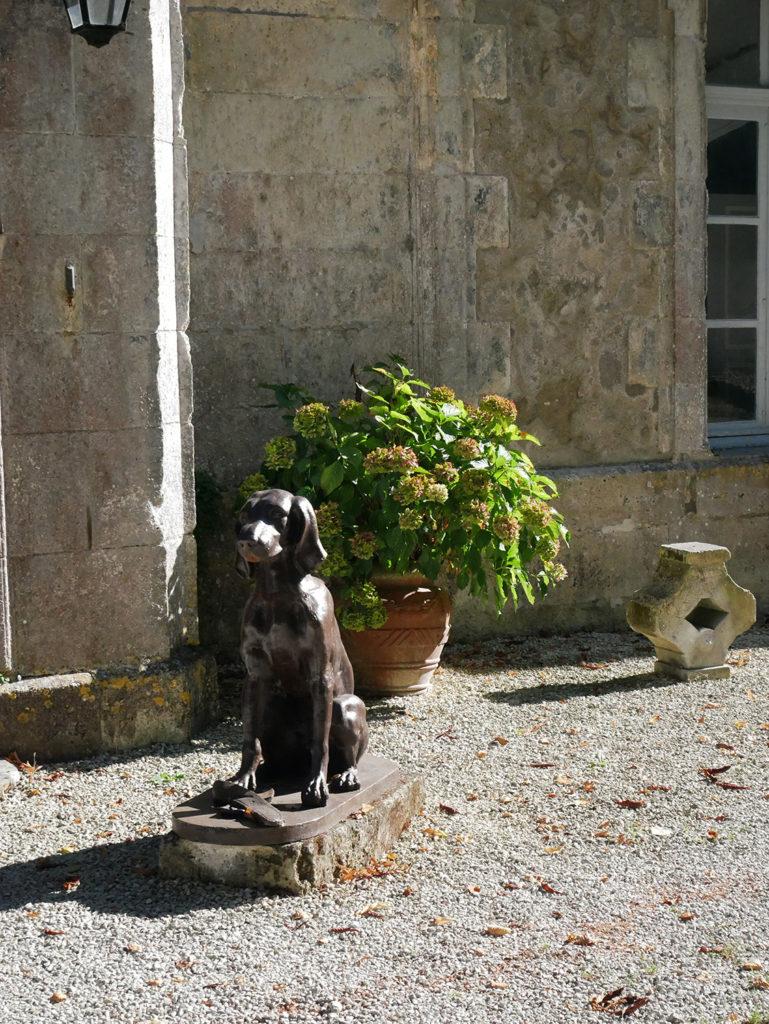 statue de chien trônant devant la façade du château de la Courade en Charente