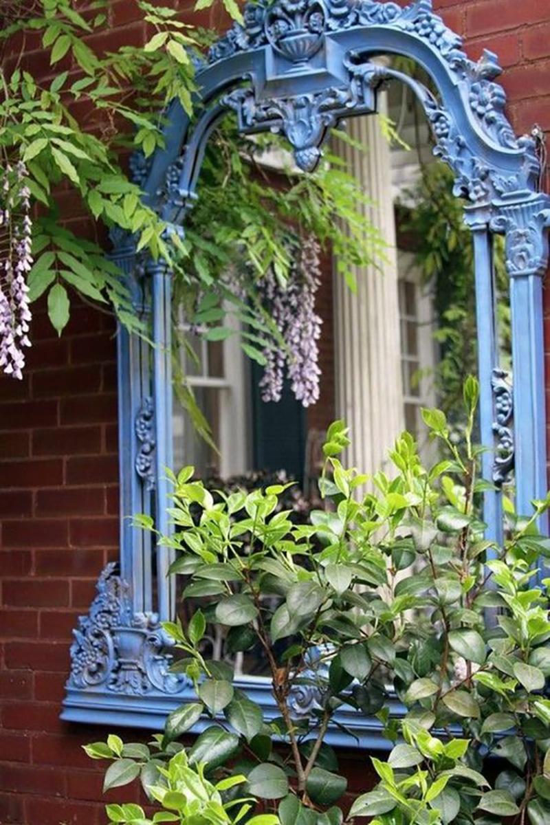 miroir baroque peint en bleu accroché sur un mur extérieur en briques