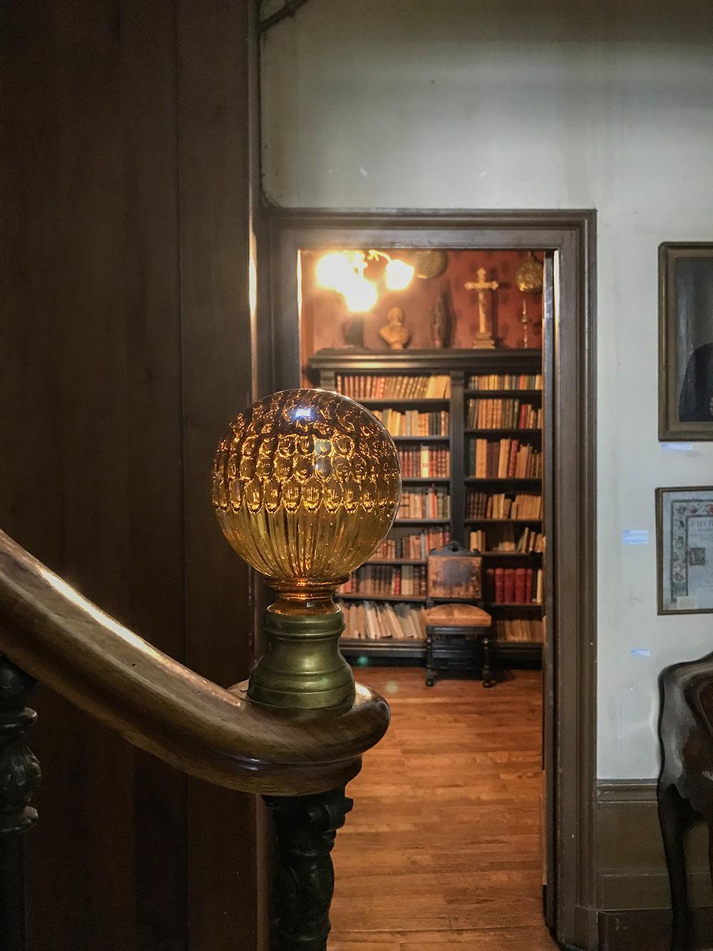 détail de boule d'escalier et vue sur entrée du bureau de Jean George