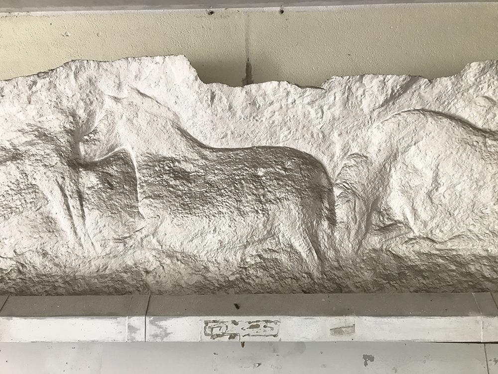 moulage d'une scène gravée dans la roche exposée dans la cave voutée sous la maison